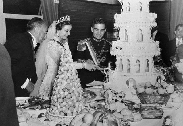 Original caption: Photo shows Jordan's King Hussein with his new bride, Queen Dina, at a reception after their recent marriage.  the new Queen cuts immense four layer wedding cake as the bridegroom (right) and Sherif Hasan (left), the Queen's uncle, watch. April 23, 1955 Amman, Jordan @
