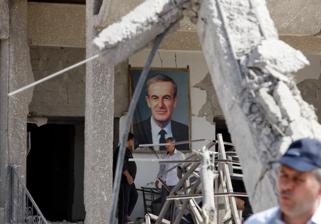 A framed portrait of Syria's late President Hafez al-Assad, father of current President Bashar al-Assad, is seen at the site of an explosion in a security building in Damascus . Two large explosions killed 40 people in Damascus on Thursday, state media said, destroying dozens of cars on a highway and damaging an intelligence complex involved in President Bashar al-Assad's crackdown on a 14-month-old uprising.  @Khaled al-Hariri/Reuters photo)