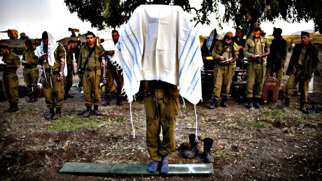 An Israeli soldier of the Golani brigade covers himself in a prayer shawl as others gather for the morning prayer before a military exercise in the Israeli controlled Golan Heights, near the border with Syria, Tuesday, May 7, 2013. © Ariel Schalit)