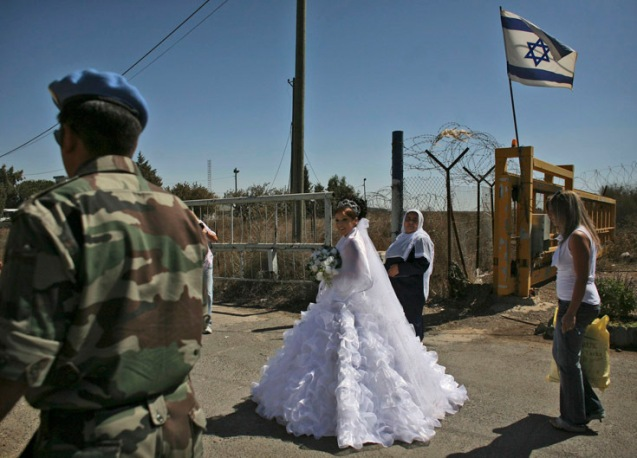 Israeli-Druze bride Arin Safadi, 24, departs through the United Nations buffer zone at the Quneitra crossing in the Golan Heights, which Israel captured from Syria in 1967, to marry a Syrian-Druze groom, Thursday, Sept. 25, 2008. Once crossing into Syria, the bride is not allowed to go back to Israel. Syria and Israel have held four rounds of indirect talks through Turkish mediation so far and Assad recently said he is looking to have direct, face-to-face talks next year. The main sticking point has been the extent of an eventual Israeli withdrawal from the Golan Heights. The issue led to the collapse of U.S.-brokered direct negotiations in 2000. Syria demands the complete return of the Heights. Israel has sought to keep a strip of land around the Sea of Galilee. ©Dan Balilty | AP