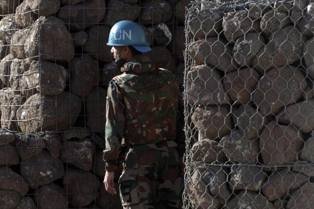 A UN soldier stands next to a shelter inside a UN base near the Quneitra crossing between the Israeli-controlled Golan Heights and Syria.  © AP FILE PHOTO