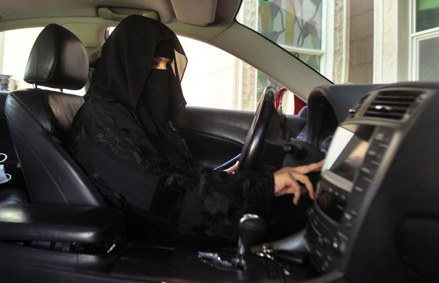 """Uma saudita, coberta de negro, da cabeça aos pés, como exige a temível Polícia para a Promoção da Virtude e Prevenção do Vício"""", desafia as autoridades conduzindo o seu próprio veículo sem motorista, geralmente imigrantes filipinos ou paquistaneses © Faisal Al Nasser   Reuters"""