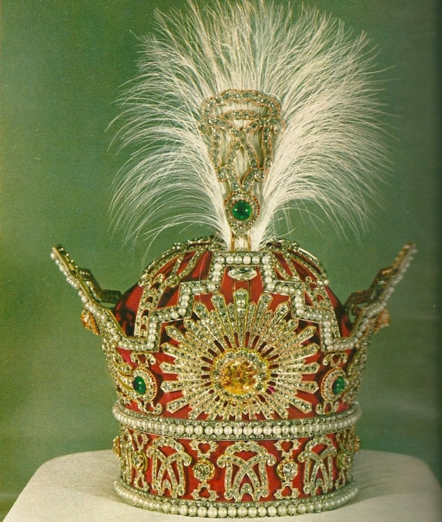 """The Pahlavi Crown was commissioned and first used for the coronation of Reza Shah on 25 April 1926. It was used for the last time during the coronation of his son and successor Mohammad Reza Shah Pahlavi on 26 October 1967. (…) The frame of the crown is made of gold, silver and red velvet. It has a maximum height of 29.8 cm, a width of 19.8 cm and weighs nearly 2,080 grams. A staggering 3,380 diamonds, (1,144 carats), are set into the object. The largest of these is a 60-carat (12 g) yellow brilliant, which is centrally placed in a sunburst of white diamonds. Found in three rows are 369 nearly identical natural white pearls. The crown also contains five emeralds (totalling 200 carats), the largest of which is approximately 100 carats and located on the apex of the crown."" © All Rights Reserved"