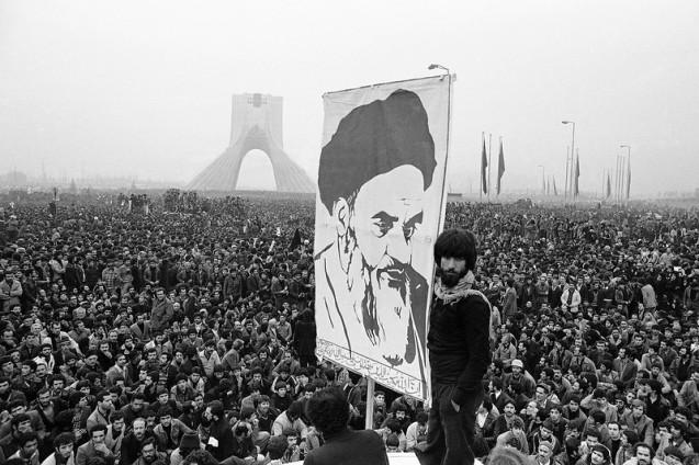 Um cartaz gigante do Ayatollah Khomeini é erguido durante uma manifestação contra o Xá, junto a um antigo monumento que assinalava os 25 anos de poder do poder do segundo imperador Pahlavi. Foi no dia 10 de Dezembro de 1978 - no ano seguinte, o teólogo exilado em França regressava à pátria para instaurar a primeira República Islâmica. @Michel Lipchitz | Associated Press (AP)