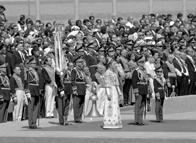 During the celebrations to mark the 2,500 anniversary of the founding of the Persian Empire, The Shah of Iran, second right, Crown Prince Riza, right, and Empress Farah, third right, watch the laying of a wreath laying ceremony at Pasargadae, Iran, Oct. 12, 1971. (AP Photo) # Farah Diba disse sim ao Xá no dia em que completou 21 anos, a 14 de Outubro de 1959. O noivado foi oficialmente anunciado a 21 de Novembro. O casamento celebrou-se a 21 de Dezembro. Yves Saint-Laurent, da casa Dior, desenhou-lhe o vestido bordado com fios de prata. O diadema para a cabeça era jóia do Estado. Concebido pelo americano Harry Winston, pesava dois quilos. @DR (Direitos Reservados | All Rights Reserved)