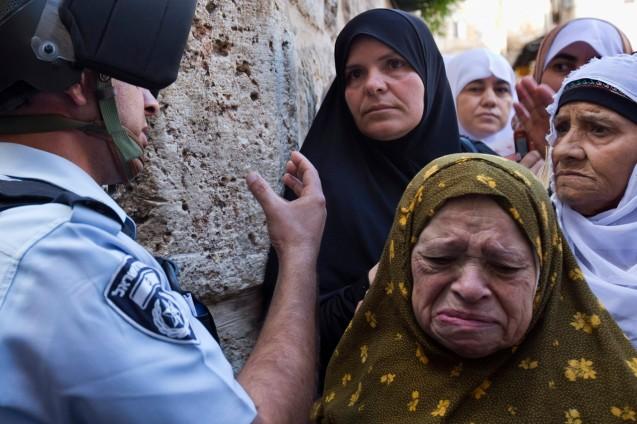Uma palestiniana chora depois de um agente da Polícia de Fronteiras de Israel informar que ela não pode entrar na Mesquita de al-Aqsa, em Jerusalém, para os judeus poderem celebrar o Rosh Hashanah, no Muro Ocidental. EPA/JIM HOLLANDER