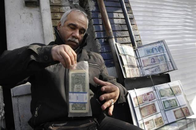 Na Rua Ferdowsi (nome de um poeta nacional), em Teerão, um homem coloca notas de dólares dos EUA num saco plástico. O seu negócio é o câmbio, mas em Dezembro de 2011, quando esta fotografia foi tirada, o valor do rial, a moeda iraniana, sofrera uma queda bruta: 1 dólar = 16,50 riais. Ainda assim, nada que se compare a 1979, o ano da Revolução Islâmica, a taxa equivalia a 1 dólar = 70 riais. @Vahid Salemi |AP |NBC