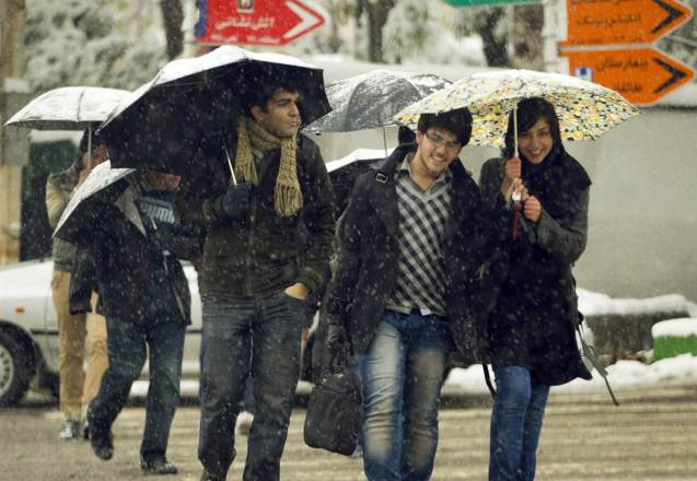 Estudantes universitários iranianos partilham chapéus de chuva, num dia de tempestade de neve (8 de Novembro de 2010), em Teerão. A inesperada neve de Outono obrigou ao encerramento de escolas e estradas na maior parte do Norte do país. @Caren Firouz | Reuters | NBC
