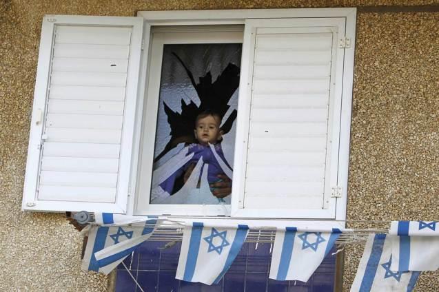 Uma criança israelita observa a rua a partir da janela da sua casa destruída por um morteiro disparado por facões palestinianas na Faixa de Gaza. @DR (Direitos Reservados   All Rights Reserved)
