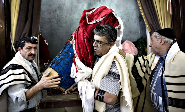 Iranian Jewish men carry the Torah scroll out from a cupboard to be read during morning prayers at Yusef Abad synagogue in Tehran on Monday. Present for more than 2,500 years in Persia, Iranian Jews have lost more than 70 per cent of their 80,000 to 100,00 population who lived in Iran before the 1979 Islamic revolution. Today Iran is home to about 8,750 Jews, according to a 2011 census. They are scattered across the country, but are mostly in the capital Tehran, Isfahan in the centre and Shiraz in the south. @Behrouz Mehri/AFP