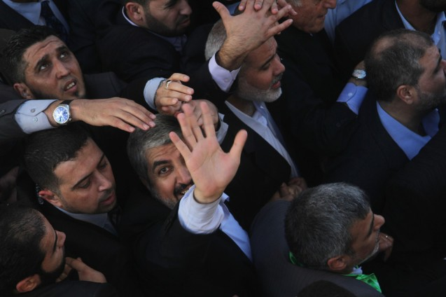 Hamas chief Khaled Meshaal and Palestinian Prime Minister in the Gaza Strip Ismail Haniyeh wave to the crowd upon his Meshaal's arrival to Gaza City, 7 December. Meshaal made his first-ever visit to the Gaza Strip amid tight security for festivities marking the ruling Hamas movement's 25th anniversary. @Ezz Al-Zanoon / APA images)