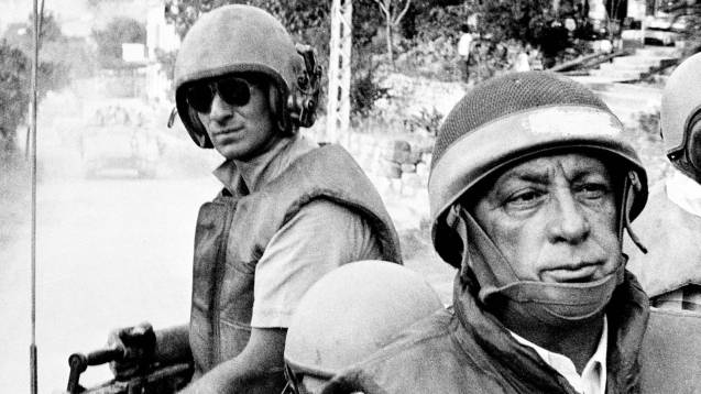 In this June 15, 1982 file picture, Israeli Defence Minister Ariel Sharon, foreground, rides an armored personnel carrier on a tour of Israeli units advancing to the outskirts of Beirut, Lebanon. (THE @ASSOCIATED PRESS / Israeli Defence Ministry / File)