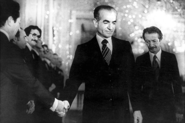 The shah of Iran Mohammed Reza Pahlavi (C) shakes hand with a minister of the new civilian government of Prime Minister Shapour Bakhtiar (R) 06 January 1979 in Teheran. The shah left his country 16 January 1979. AFP PHOTO (Photo credit should read . @ AFP/Getty Images)