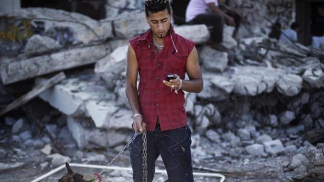 Um jovem lê mensagens no seu telemóvel, em Trípoli, 28 de Outubro de 2011. A Líbia planeia lançar em 2014 um concurso para o funcionamento da primeira operada privada de telecomunicações. © AFP