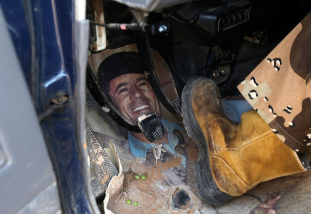 An anti-Qaddafi fighter uses a picture of Muammar Qaddafi as a floor mat in his vehicle at El-Khamseen gate, the eastern gate of Sirte, on September 25, 2011. @ Reuters/Asmaa Waguih)