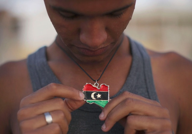 Mohammed Sayad, 18 anos, exibe o seu colar com uma bandeira anterior à da República Popular proclamada por Khadafi. @Alexandre Meneghini | AFP