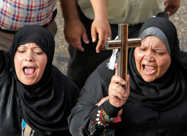 Egyptian Muslim women hold a cross in support of Christians during a memorial march in Cairo for Christians who were killed during deadly clashes with Muslims in April. ©Amr Nabil / AP file
