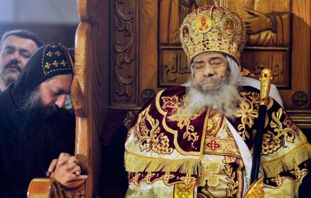 Oração de um copta junto ao corpo do Papa Shenouda III, líder da Igreja Copta Ortodoxa do Egipto, exposto ao público para as devidas homenagens, na catedral de Abbasiya no Cairo (18 de Março de 2012). © Esam Al-Fetori | Reuters