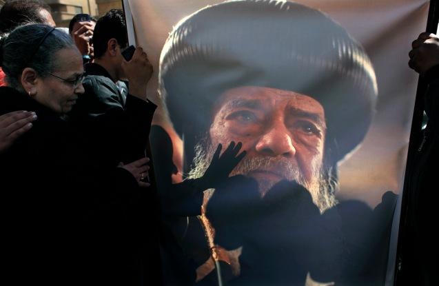 Fiéis coptas despedem-se do líder espiritual. Mãos tocam a foto do Papa Shenouda III, erguida numa igreja no Cairo, durante as exéquias fúnebres, a 18 de Março de 2012. © Nasser Nasser |AP