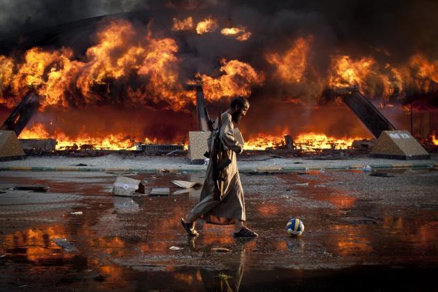 Um rebelde líbio joga à bola num cenário de guerra, em 2012. © Philippe de Poulpiquet | Photographie.com
