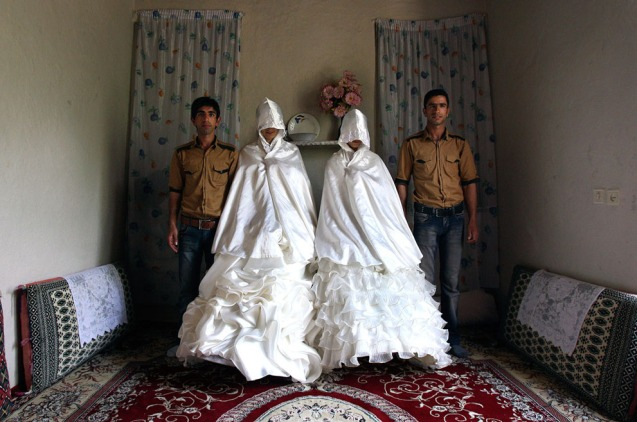 Iranian grooms, Javad Jafari, left, and his brother, Mehdi, right, pose for photographs with their brides, Maryam Sadeghi, second left, and Zahra Abolghasemi, who wear their formal wedding dresses prior to their wedding in Ghalehsar village, about 220 mi (360 km) northeast of the capital Tehran, Iran, on July 15, 2011. @AP Photo/Vahid Salemi)
