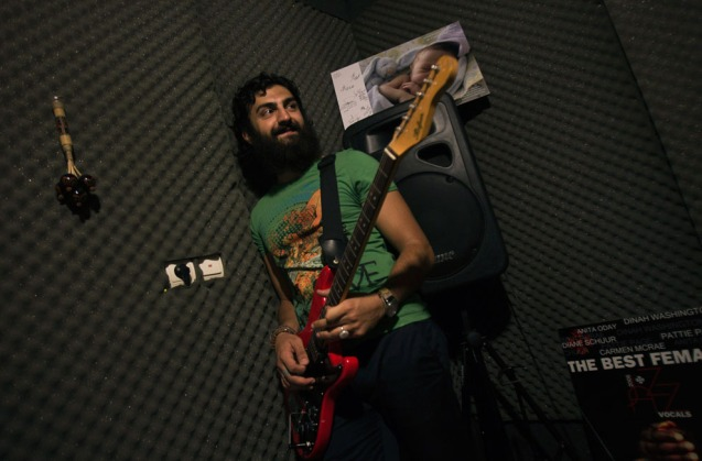 "Sevan Shahmirian, a member of the underground music band ""Wednesday Call"" prepares for a practice session at a home music studio in Tehran, on July 7, 2011. Many Iranian bands do not bother asking for the mandatory government permits to release their music and seek contracts with foreign companies or put their music on websites blocked by the state but still accessible to anyone with a modicum of technical skill. @Reuters/Morteza Nikoubazl)"