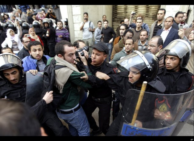 Egyptian anti-riot policemen block the way in front of a photojournalists standing outside a journalists syndicate in downtown Cairo. @