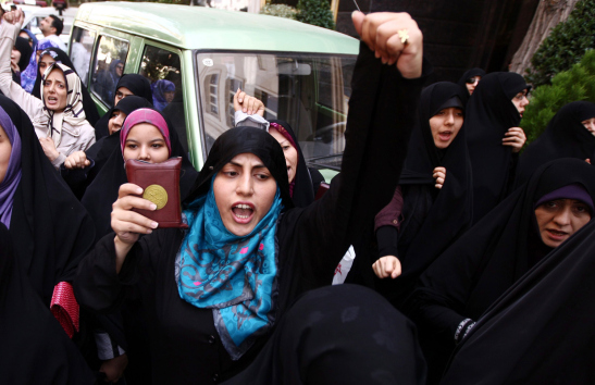 An Iranian Islamist female shouts anti-U.S. slogans while holding a copy of the Quran in front of the U.S. interest section within the Swiss embassy in Tehran, Iran, Sept. 13 2012. Reports state some 500 Iranian Islamists gathered to protest against an anti-Islam film made in the U.S. © Direitos Reservados | All Rights Reserved