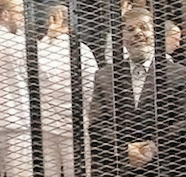 Ousted President Mohammed Morsi stands with his co-defendants in the defendant's cage in a makeshift courtroom in Cairo, Egypt, Monday. The trial was adjourned until Jan. 8. Photograph by: Associated Press Photo, Egyptian Interior Ministry , @The Associated Press Read more: http://www.vancouversun.com/news/Ousted+president+defiant+court/9126036/story.html#ixzz2sV9ts6Lm