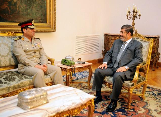 13 de Agosto de 2012: Abdel-Fattah el-Sisi (à esquerda) é recebido pelo Presidente Mohamed Morsi, que o promoveu a ministro da Defesa. Foi uma aliança de curta duração, porque o general rapidamente destituiu e mandou prender o sucessor de Hosni Mubarak, aspirando aa ocupar o seu lugar. @ AP | Egyptian Presidency