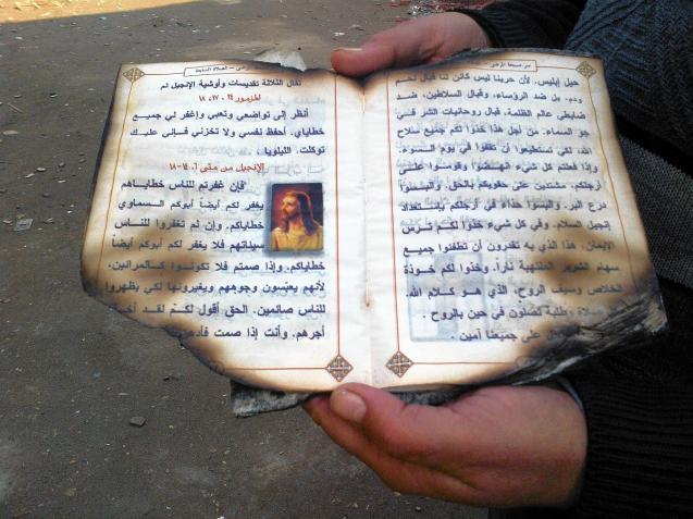 Um paroquiano copta mostra páginas de um livro de orações resgatado deppis de um ataque sectário à Igreja do Arcanjo Gabriel, no Egipto. @ Laura King |Los Angeles Times