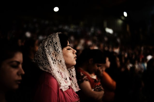 "Worshippers attend a service as Coptic priest Father Samaan Ibrahim reads his sermon on July 26, 2012 at the St Samaans (Simon) Church also known as the Cave Church in the Mokattam village, nicknamed as ""Garbage City,"" in Cairo. Once a week hundreds gather at the Cave Church in Moqattam, after the prayer, a coptic priest performs exorcism or healing blessing to some of the believers. With a cross and holy water he fights spiritual entities and demons. The Monastery of St. Simon the Tanner is the largest and it has an amphitheater with a seating capacity of 20,000 making it the largest church in the Middle East. It is named after the Coptic Saint, Simon the Tanner, who lived at the end of the 10th century, when Egypt was ruled by the Muslim Fatimid Caliph Al-Muizz Lideenillah. Simon the Tanner is the Coptic Saint who is associated with the legend of the moving of the Mokattam Mountain. AFP PHOTO/GIANLUIGI GUERCIA @ GIANLUIGI GUERCIA/AFP/GettyImages)"