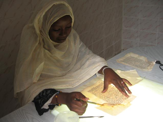 A woman preserves ancient manuscripts in the library at Timbuktu. @Richard Kurin