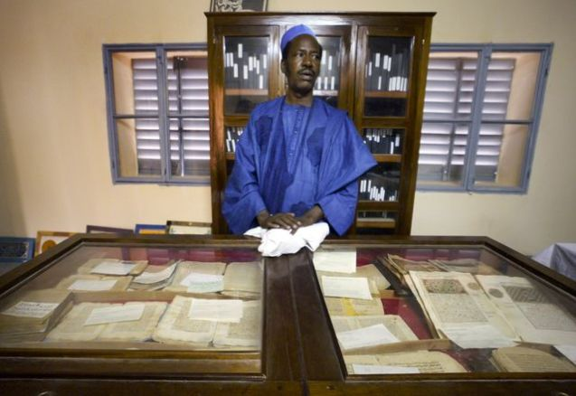 An unidentified worker looks after some of the 20,000 preserved ancient Islamic manuscripts that rest in air-conditioned rooms at the Ahmed Baba Institute in Timbuktu, Mali, in 2004. @Ben Curtis | AP Photo