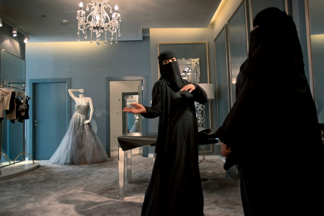 "Two Saudi saleswomen in Harvey Nichols, the British luxury department store, in Riyadh. In 2011, the Ministry of Labor ordered shops specializing in cosmetics, abayas, and wedding dresses, along with the women's sections of department stores, to begin shifting to all-female Saudi sales staffs. The process is called ""feminization."" @Kate Brooks Photography 