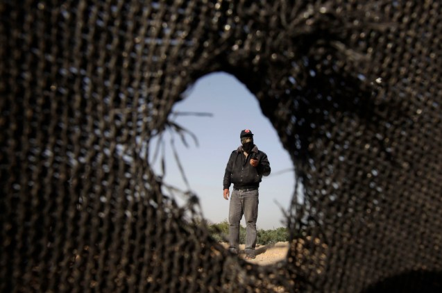 A Palestinian militant of the Democratic Front for the Liberation of Palestine (DFLP) inspects a training base after it was hit by an Israeli air strike in Rafah