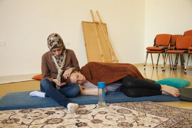 """Anat Shuhman, que primeiro ponderou ser refusenik, diz a Noor que aceitou fazer """"serviço cívico"""" para perceber """"por que é preciso sacrificar três anos de vida no Exército"""". Enquanto a palestiniana lhe afaga os longos cabelos vermelhos, a garota que vive no colonato, """"apenas porque a renda de casa é mais barata"""", adapta uma citação, de autor que não recorda, para resumir a missão de ambas: """"Todas as mudanças começam com uma minoria que muitos consideram loucos, mas serão loucos a mudar o mundo."""" © Udi Goren"""
