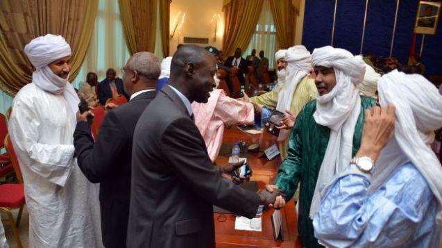 Membros de delegações do Mali e dos Tuaregues cumprimentam-se após a assinatura de um acordo de cessar-fogo, em Ouagadougou, capital do Burkina Faso, em 18 de Junho 18 de 2013. @DR (Direitos Reservados | All Rights Reserved)