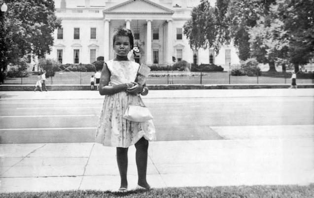 Condoleeza Rice stands in front of the White House as a girl.