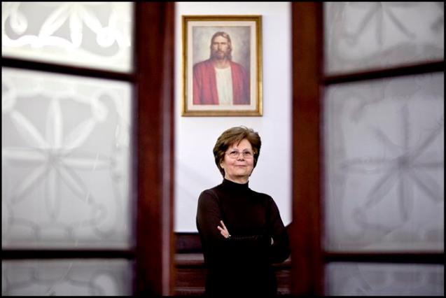 """Maria José Gonçalves na capela mórmon em Lisboa; atrás de si está uma imagem com grande significado a SUD. O pintor terá mostrado a obra ao fundador da Igreja, Joseph Smith, que, depois de """"visões de Deus e de Jesus"""", lhe disse: """"Não estás longe do rosto verdadeiro"""" @NUNO FERREIRA SANTOS"""