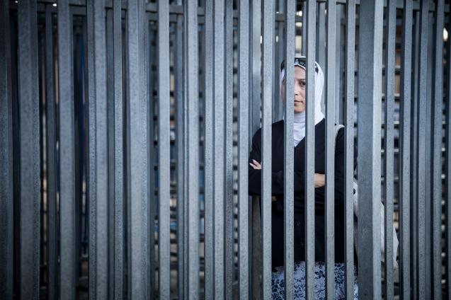 """Nibal Raj, palestiniana, 42 anos, viúva, uma só filha, formada em Sociologia da Educação, co-directora do Sulha Project, com a israelita Dafna Schwartz: """"Às sextas-feiras, os soldados só nos deixam passar no checkpoint de Qalandiya - na foto - , que ela atravessa diariamente] depois das orações nas mesquitas em Jerusalém. Os militares têm medo da violência que escape ao seu controlo, e estão confusos. Não nos conhecem. É difícil destruir o muro interior que nos divide."""" © Udi Goren"""