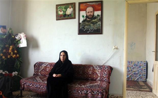 Fatima Merhi, uma mãe xiita síria de 77 anos, deixa-se fotografar no seu refúgio no Líbani, junto de um quadro com a imagem do filho Radwan, um elementos das forças rebeldes morto em Damasco, em Maio de 2013. @Ruth Sherlock | The Telegraph