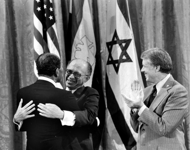 Egyptian President Anwar Sadat, left, and Israeli Prime Minister Menachem Begin, embrace as President Jimmy Carter looks on during a White House announcement of a Middle East peace agreement reached at the Camp David Summit in this September 18, 1978 file photo.  @AP Photo)