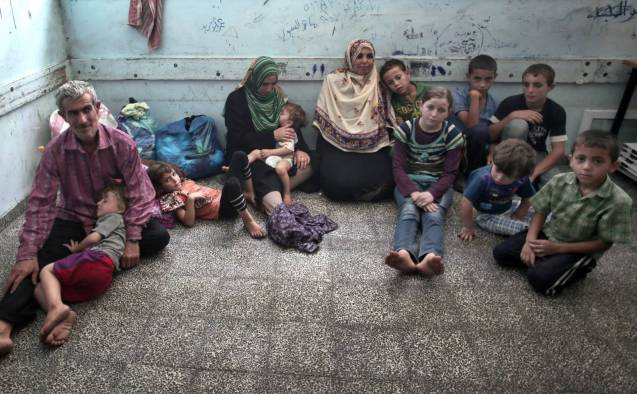 Sisters Mariam Attar, centre right, and Sada Attar, centre left, rest with their children inside the New Gaza Boys United Nations School. © The Associated Press