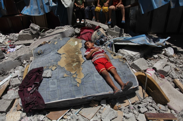 Palestinian children amid the ruins of a house destroyed by an Israeli airstrike in Gaza City, 15 July. © Ezz Zanoun | APA images