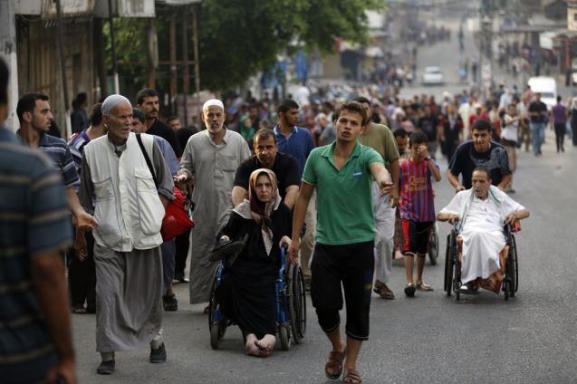 Palestinianos fogem das suas casas em Shejaiya, no sector oriental da Faixa de Gaza, em 20 de Julho de 2014, depois de violentos bombardeamentos da artilharia israelita. Muitos mortos jaziam nas ruas, Segundo reporters no local. As ambulâncias foram incapazes de chegar à area devido à intensidade do tiroteio. © Mohammed Abed |AFP | Getty Images