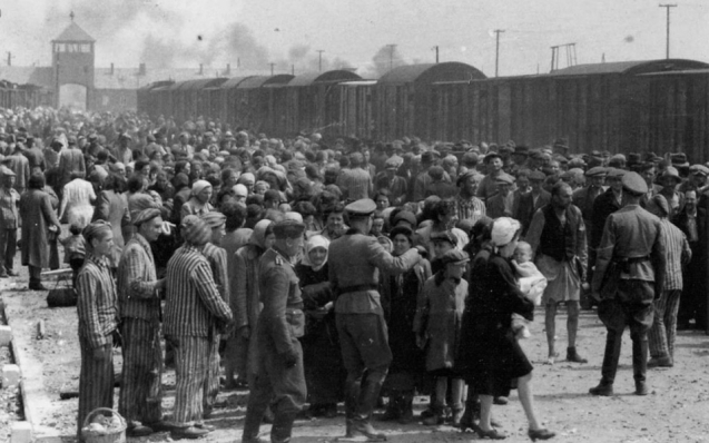 Newly arrived prisoners at Auschwitz are sorted by guards into groups of who will be sent to labour camps and who will be sent to the gas chambers. © Vashem | AP