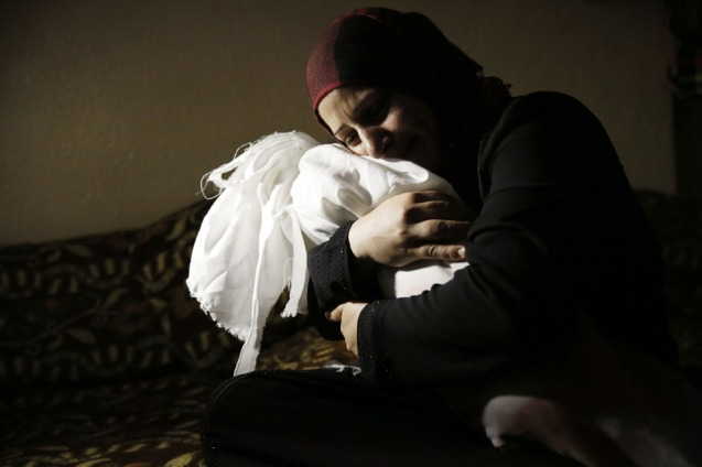 Netream Netzleam conforta o corpo da sua filha Razel, de 1 ano, que médicos disseram ter morrido de ferimentos sofridos num ataque israelita em Rafah, no sul da Faixa de Gaza the southern Gaza, em 18 de Julho de 2014. © Finbarr O'Reilly