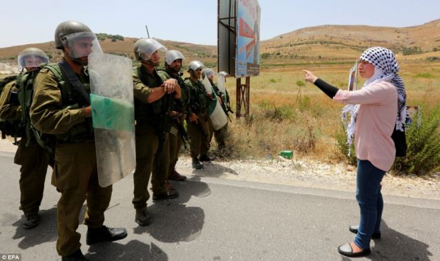 A Palestinian woman shouts at Israeli soldiers as she confronts them during a protest against the Israeli attacks on Gaza Strip at the Howwara checkpoint today © EPA