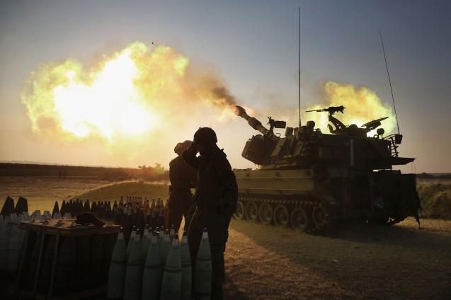 Soldados israelitas disparam canhões de artilhara de 155 milímetros em direcção à Faixa de Gaza, a partir da sua base na fronteira, a 21 de Julho de 2014. © Menahem Kahana/AFP/Getty Images